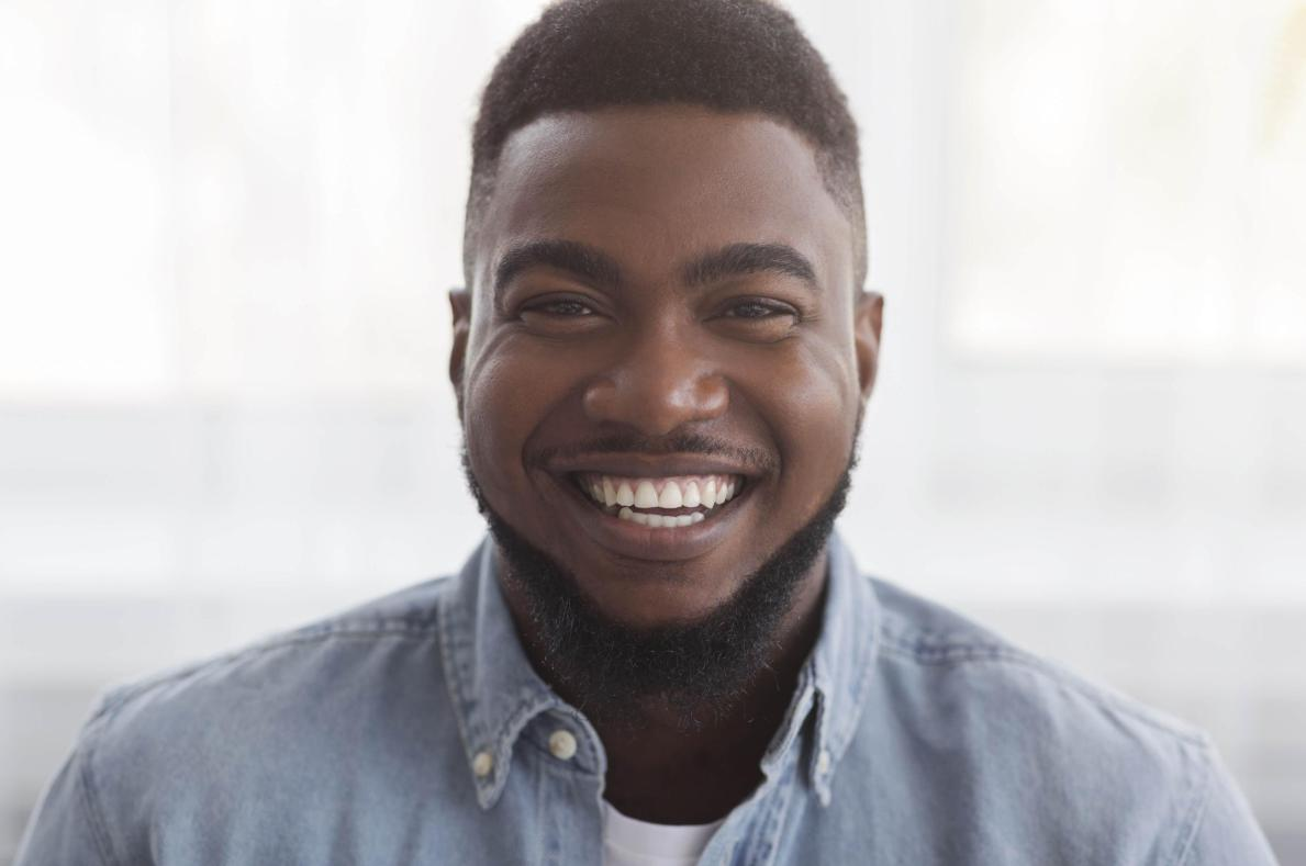 Black male professional wearing blue shirt in cannabis startup office smiling