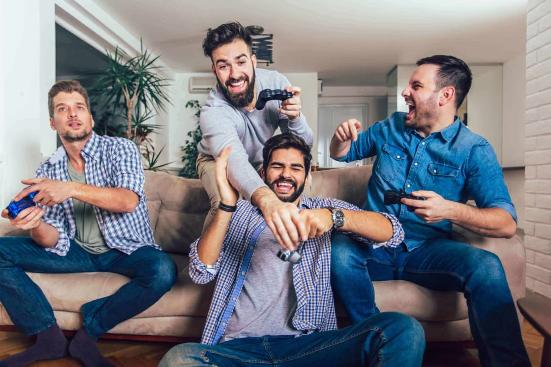 Four male co-workers at cannabis startup play video games while working from home remotely