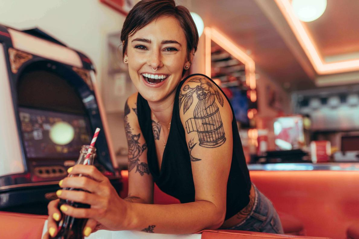 Tattooed female budtender takes a break drinking a soda at a dispensary in front of arcade video games