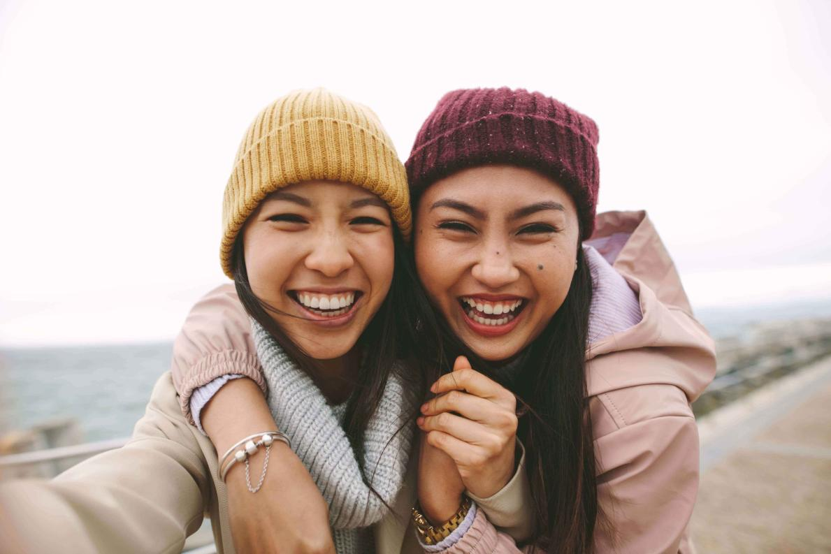 Two asian female coworkers wearing hats outside take a walk by the ocean in northern California after visiting a local cannabis dispensary