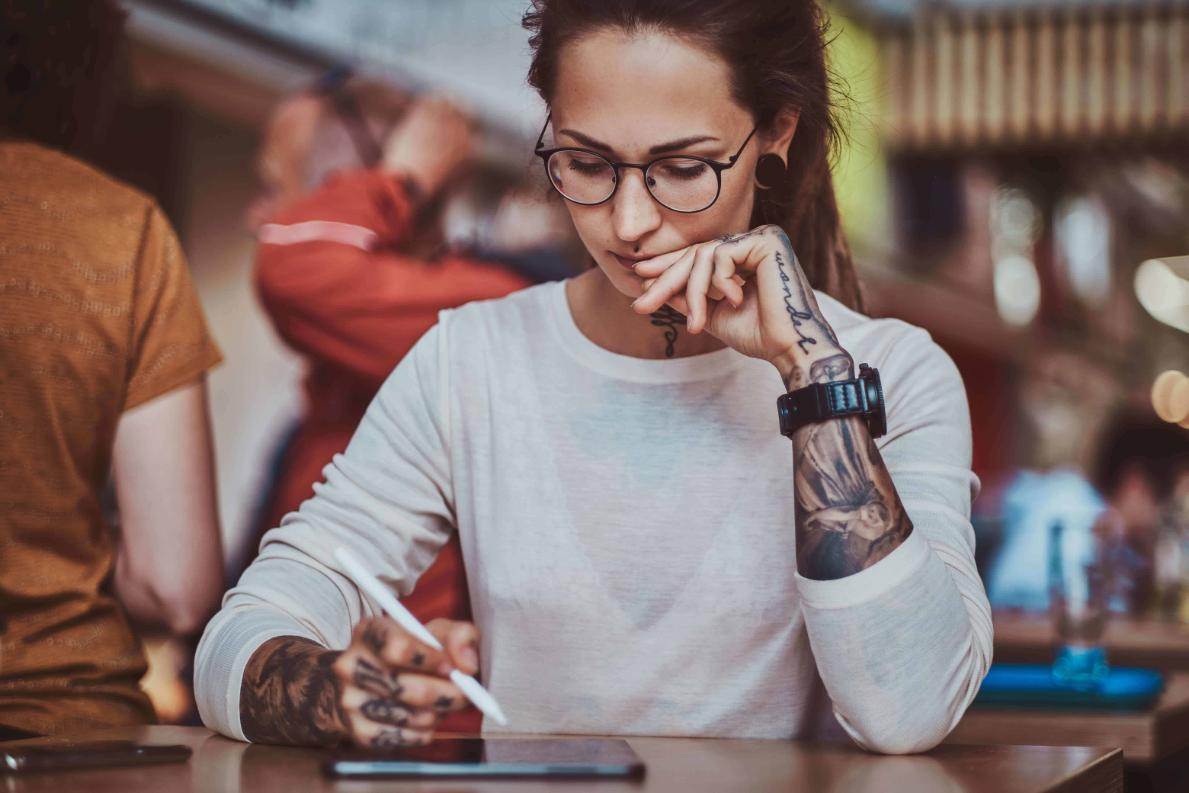 Female with tattoos sits in a marijuana cafe looking for a cannabis dispensary job on her tablet online