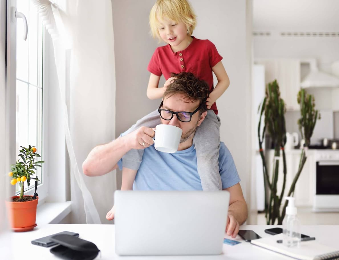 Work from home frustrated father sits at his desk with a laptop open while son plays on his shoulders playing with his hair and eyeglasses while working remote